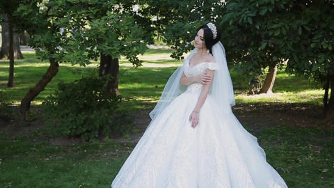 A very beautiful bride stands alone in the park, worries while waiting for the Footage