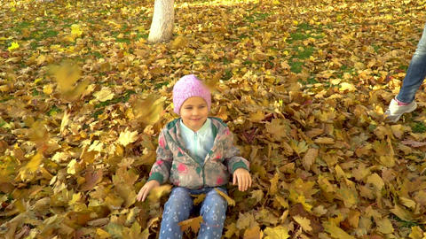A little girl bathes in fallen autumn leaves ビデオ