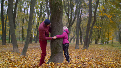 Joyful father and kid playing hide and seek in autumn Footage