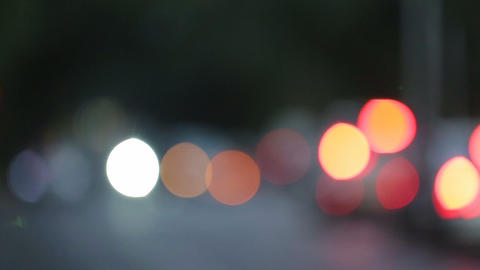 Road traffic in evening city, blurred light spots changing into car headlights Footage