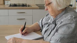 Senior woman is writing letter or the last will Live Action