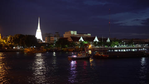 Large buddhist stupa for prayer light up on coastline of river at night time Footage