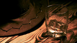 A glass of whiskey and a cowboy hat on the table Texas style ビデオ
