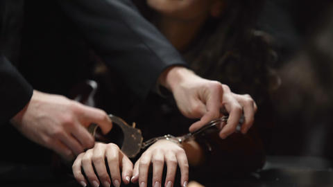 Impudent and self-confident prostitute in handcuffs waiting for interrogation Live Action