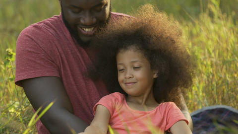 Father looking at daughter with love, spending time in park, happy childhood Footage