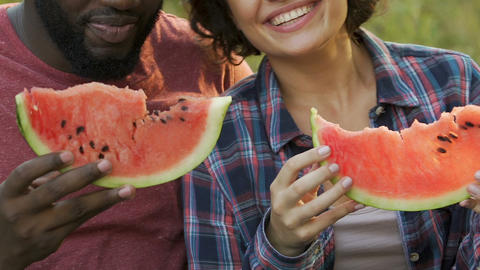 Couple tasting fresh watermelon during outside date in park, healthy nutrition Live Action