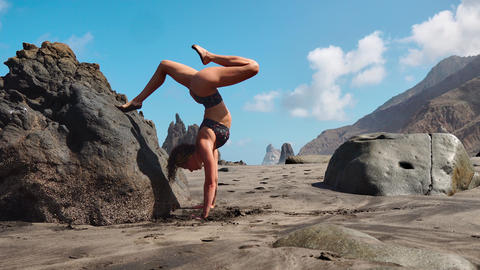 Calm girl is meditating in the mountains, bright sunshine on the background. In Live Action