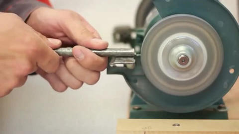 Carpenter working with electric machine, grinding metal drill ビデオ