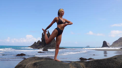 Girl doing yoga balancing on one leg standing on a stone. Peace of mind. Healthy Footage