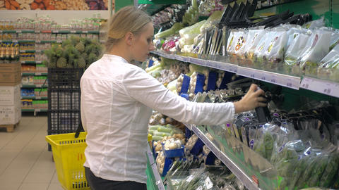 woman in a supermarket at the vegetable shelf shopping Footage