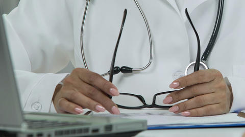 Female therapist hands holding eyeglasses, physician reading e-mail on laptop Live Action