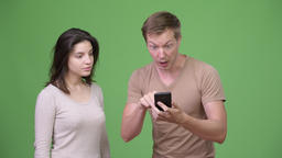 Young man using phone with young woman looking shocked Footage