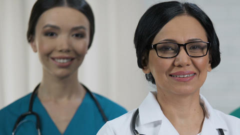 Friendly female medical staff smiling at camera, health care system, profession Live Action