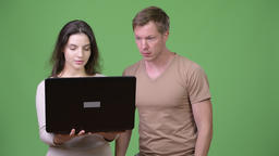 Young woman using laptop with young man looking shocked Footage