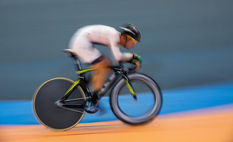 Profile blurred motion of cyclist competing indoor Photo