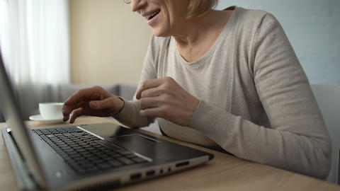 Smiling aged lady typing message on laptop, communicating on dating website Live Action