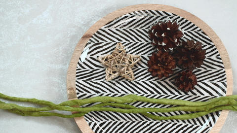 Modern Christmas composition. Dish with black and white herringbone pattern, straw star, conifer Live Action
