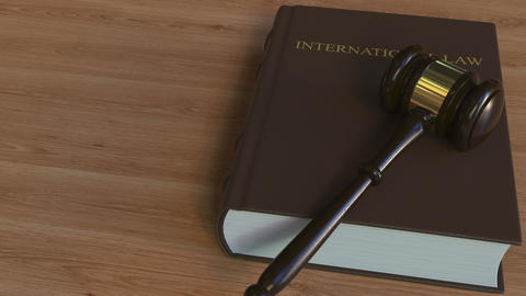 INTERNATIONAL LAW book and judge's gavel. Conceptual 3D animation Live Action