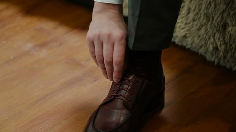 Man tying patent leather shoes formal and festive dressing Live Action