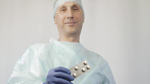 The doctor shows the patient a package of pills. And a gesture shows that it is Footage