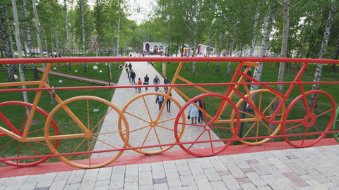 view from bridge with bicycle handrails on people in park Footage