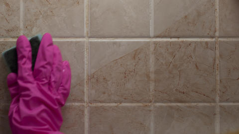 Close up shot of cleaning the dirty tile wall with hand in rubber glove by Footage