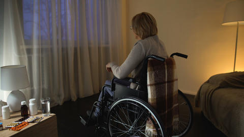 Disabled woman in wheelchair looking through the window on street, loneliness Live Action