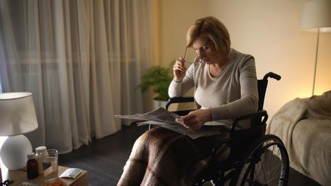 Grandmother trying to read newspaper in eyeglasses, eye… Stock Video Footage