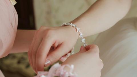 the bride wears wedding jewelry, put bracelet on wrist Footage