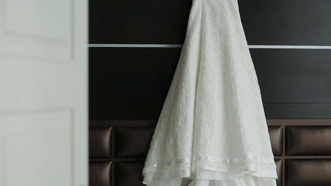 Wedding dress hanging in a white beautiful room Archivo
