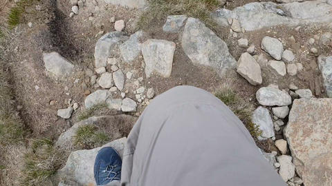Footsteps of the man that goes down from the mountain in slow motion GIF