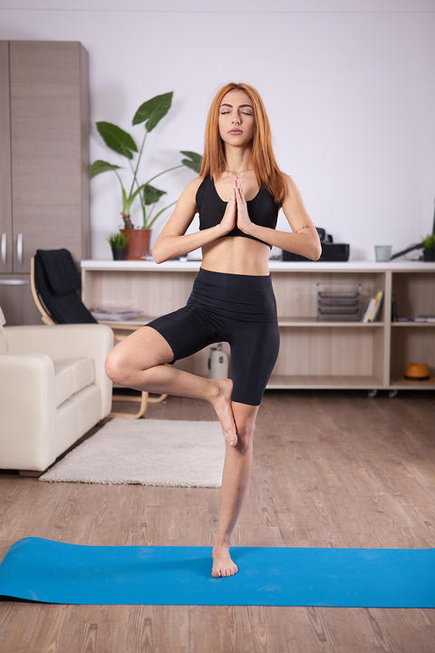 Blonde girl relaxing her body and mind in Tree yoga pose Photo