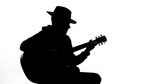 Young male in hat playing musical instrument at party, art hobby, recreation Footage