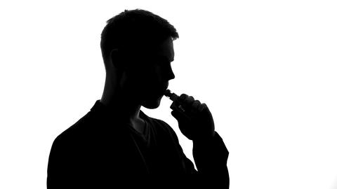Male shadow smoking electronic cigarette, modern device creating tobacco feeling Live Action