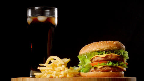 burger with french fries and a glass with ice cola on a... Stock Video Footage