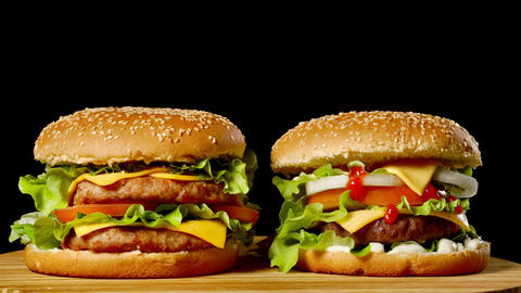 Close-up of two appetizing burgers with sesame buns rotating on black background Live Action