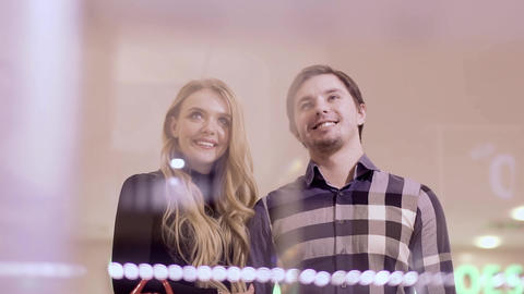 A beautiful blonde and her boyfriend stop by the shop window Footage