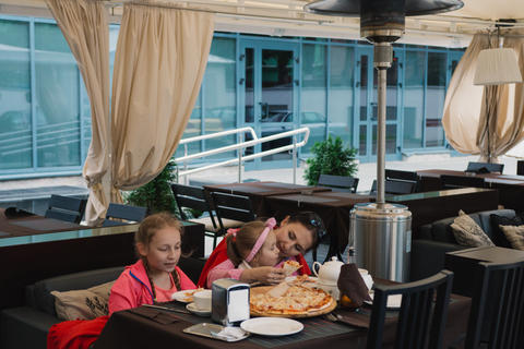 Mom and children eating pizza at a cafe Photo