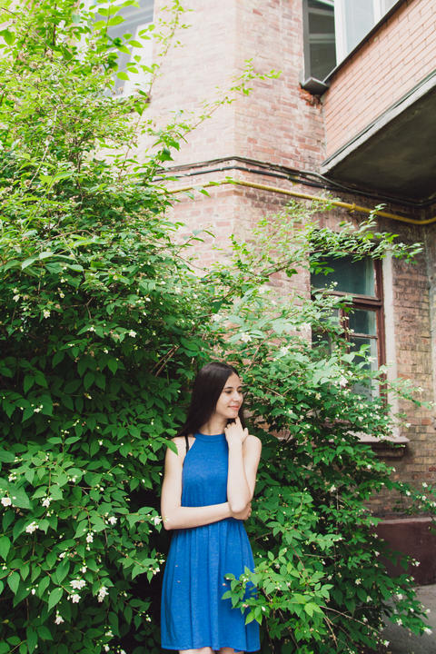 A very beautiful and cheerful girl stands on the street near a bush with white Photo