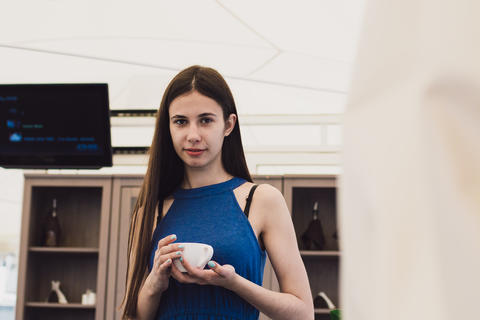 A very beautiful business woman sits in a cafe and holds a cup of coffee in her Photo