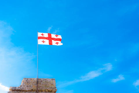 Flag of Georgia on a background of blue cloudy sky Fotografía