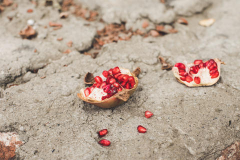 Ripe red pomegranate on the stone surface フォト
