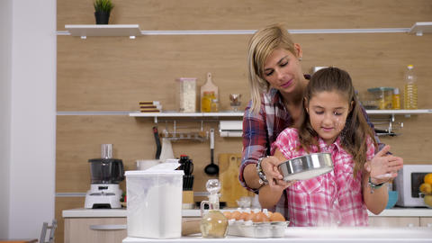 Mother and daughter cooking together in the kitchen Live Action