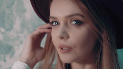 Blue-eyed girl model in black hat. Close up. Slow motion Footage