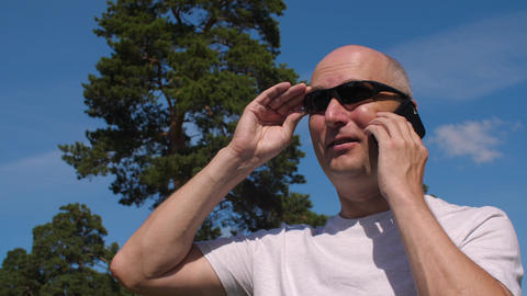 Bald man wearing glasses calling by mobile phone on summer park background GIF