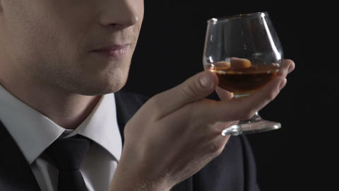 Politician enjoying taste of cognac and smiling, celebrating successful deal Live Action