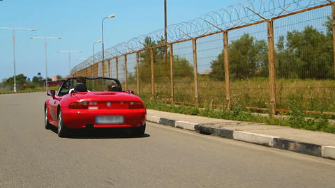 Young couple enjoying high speed ride in red convertible auto, carefree life Live Action