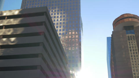 Driving through downtown office buildings into morning sun Footage