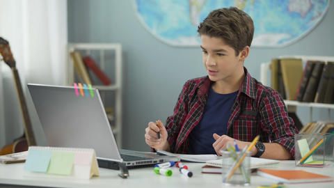 Smart teenage kid diligently doing homework tasks to achieve success in future Live Action