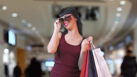 A beautiful brunette in a mall looks coquettish from under the glasses. Day of Live Action
